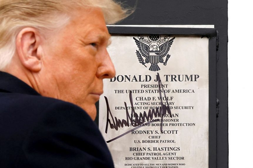 President Donald Trump signing a plaque placed at the US-Mexico border wall in Alamo, Texas, Jan 12, 2021.