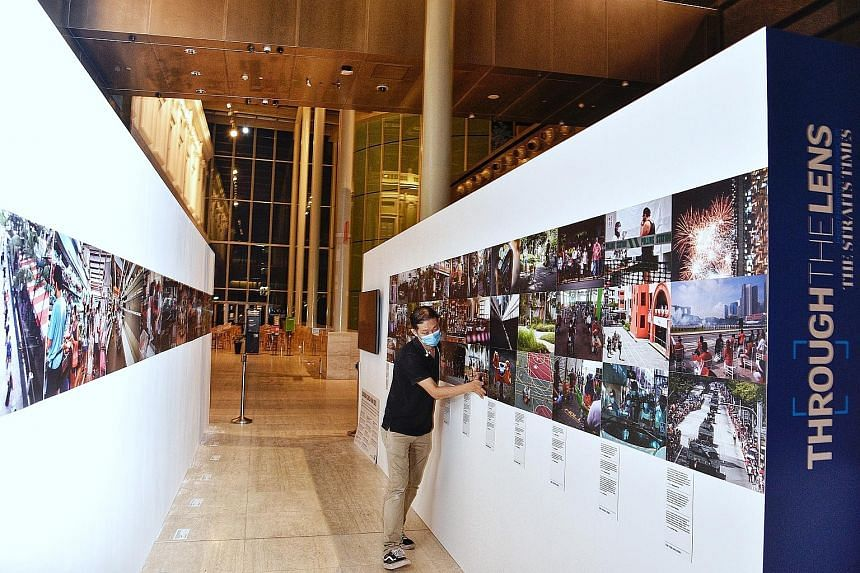 An employee setting up an exhibit last night at Through The Lens, a photography exhibition by The Straits Times and World Press Photo (WPP). It will feature ST photojournalists' coverage of the Covid-19 pandemic here, as well as photos submitted for