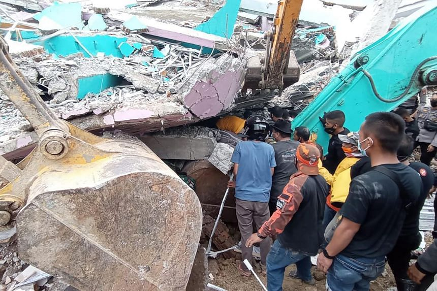 Rescuers search for survivors at a collapsed building in Mamuju city, on Jan 15, 2021.