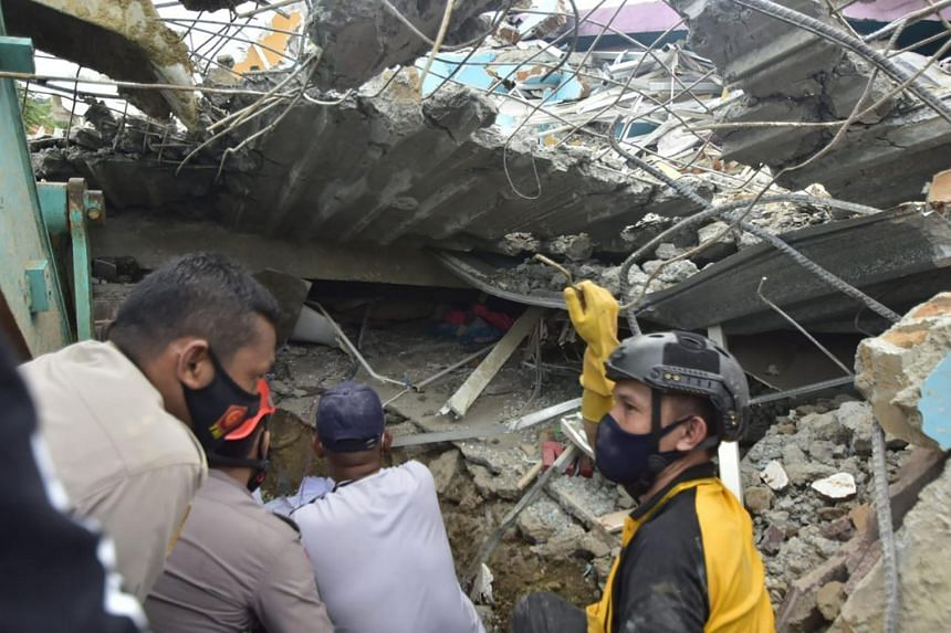 Rescuers search for survivors at the Mitra Manakarra hospital in Mamuju city, on Jan 15, 2021.