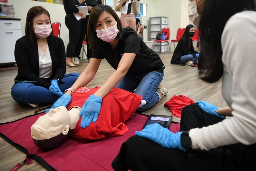 Ms Denise Ng, chief instructor for CPR+AED and assistant manager of Heart Safe (centre), teaching how to administer CPR on the new female CPR manikin vest at the Singapore Heart Foundation on Jan 15, 2021.