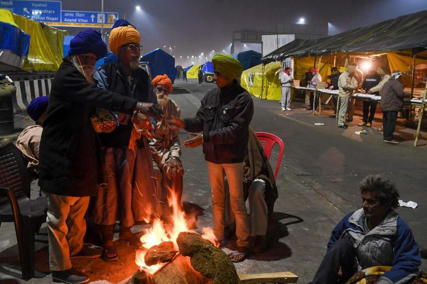Farmers celebrating the Lohri festival around a bonfire, as they continue their protest along a blocked highway in Ghaziabad on Jan 13, 2021.