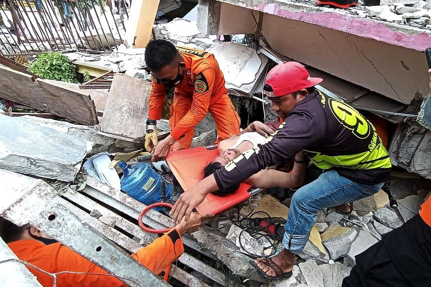 Rescuers evacuating a man from a building that collapsed in Mamuju, West Sulawesi, yesterday. PHOTO: REUTERS Rescuers (left) searching for survivors at the site of a collapsed building in Mamuju city. A hospital (right) in the Indonesian city was als