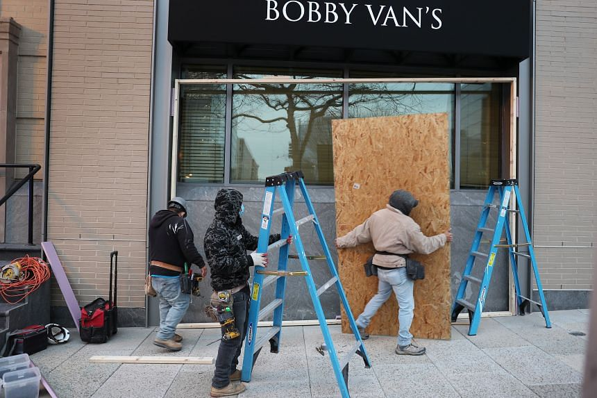 Workers board up windows of businesses before the possibility of violent protests in Washington, on Jan 15, 2021.