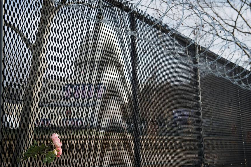 A flower rests on the raze wire fencing that now surrounds the US Capitol ahead of the inauguration in Washington, on Jan 15, 2021.