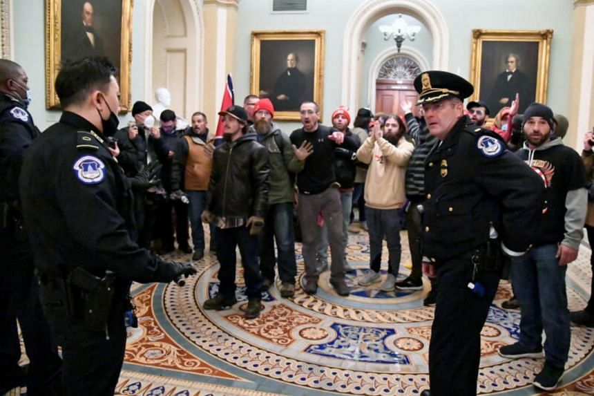Police speak to supporters of US President Donald Trump as they demonstrate on the second floor of the US Capitol in Washington, on Jan 6, 2021.