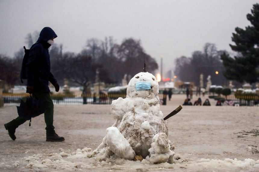 A man walks past a snowman in Paris shortly before a nationwide curfew starts, from 6pm to 6am, on Jan 16, 2021.