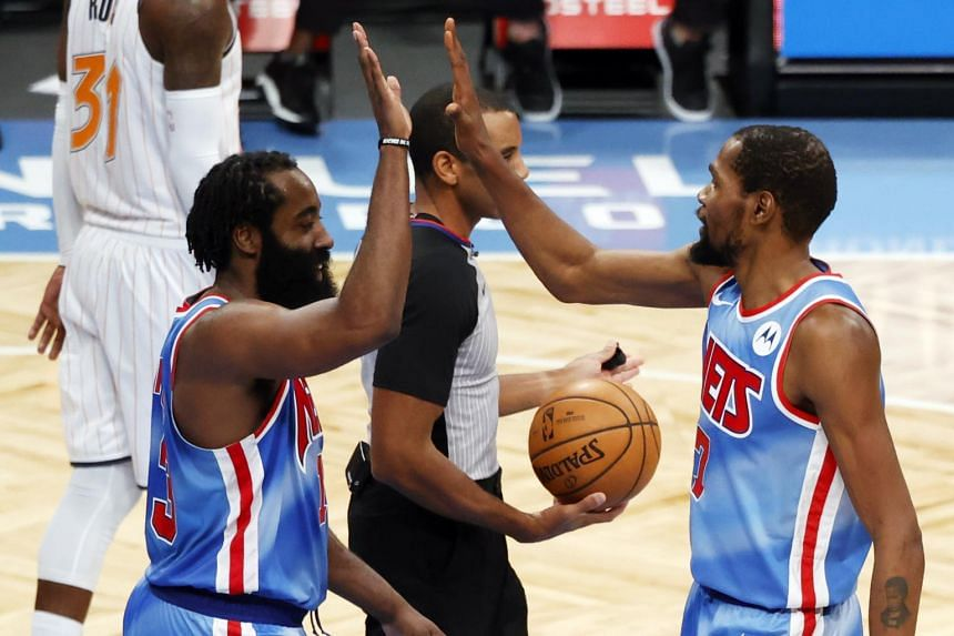 Brooklyn Nets forward Kevin Durant (right) and guard James Harden exchanging high-fives during their NBA match on Jan 16, 2021.