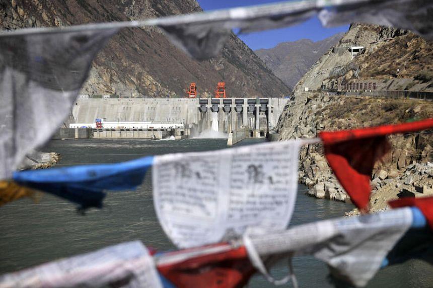 Prayer flags are seen hanging near the Zangmu Hydropower Station in Gyaca county in Lhoka, in southwest China's Tibet region, on Nov 23, 2014.