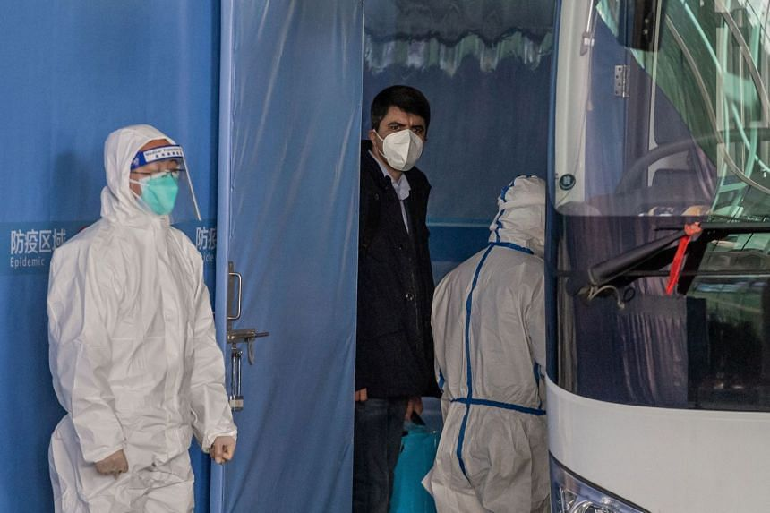 Vladimir G. Dedkov (centre), a member of the World Health Organisation team investigating the origins of the Covid-19 pandemic, boards a bus in Wuhan on Jan 14, 2021.