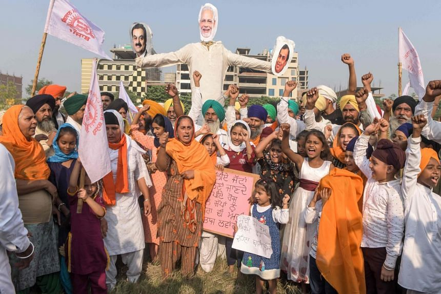 Farmers are seen with effigies of India's Prime Minister Narendra Modi, and businessmen Gautam Adani and Mukesh Ambani, during a demonstration in Amritsar on Oct 23, 2020.
