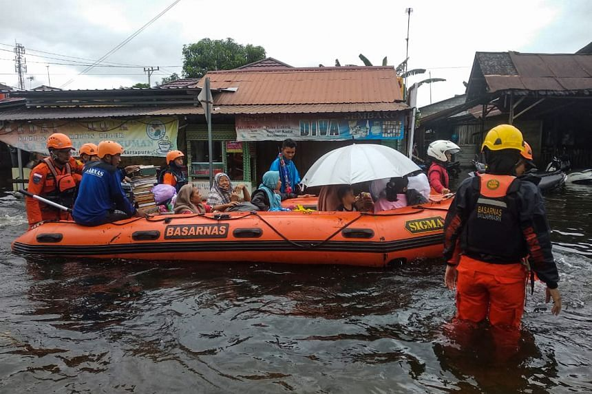 Rescuers evacuate people from a flooded residential area in Indonesia's South Kalimantan province on Jan 17, 2021.