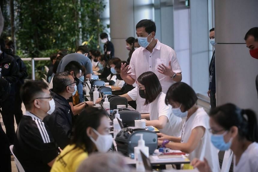 Transport Minister Ong Ye Kung speaks to air crew and front-line airport workers in the vaccination registration area at Changi Airport Terminal 4 on Jan 18, 2021.