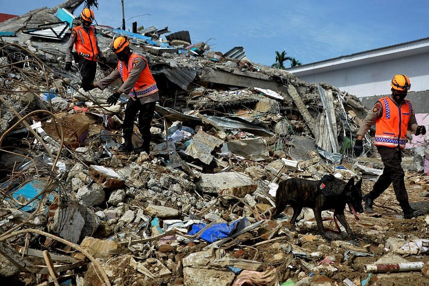 Top: Indonesian police officers searching for victims yesterday among the ruins of a hospital building, following an earthquake in Mamuju, West Sulawesi province. Above: Indonesian President Joko Widodo in South Kalimantan yesterday. He inspected dam
