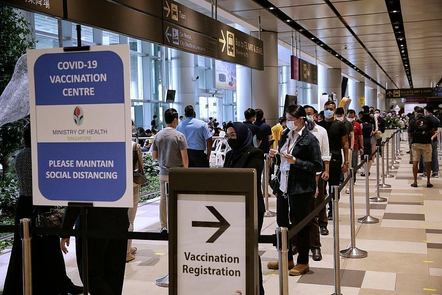 Front-line workers in the aviation industry registering for Covid-19 vaccination at Changi Airport Terminal 4 yesterday. Inoculating front-line workers will also protect Singapore, Transport Minister Ong Ye Kung said, noting that while the situation