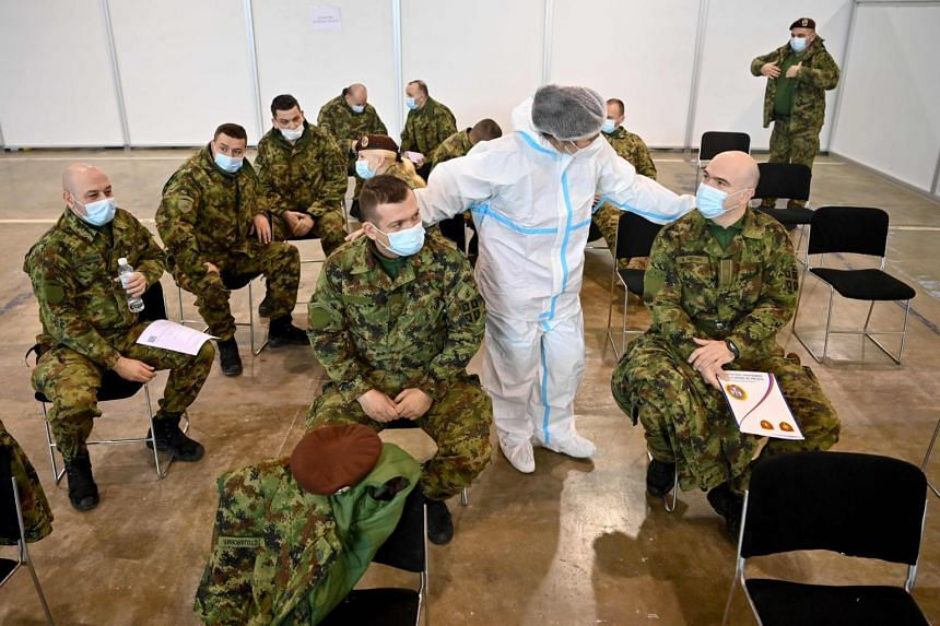A medical worker checks Serbian army personnel after they received the Chinese-made Sinopharm vaccine in Belgrade, on Jan 19, 2021.