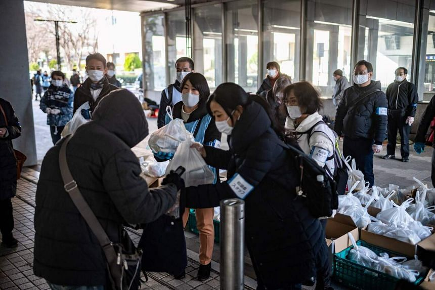 Volunteers give out food handouts to people in need in Tokyo on Jan 9, 2021.