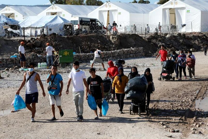 Refugees and migrants make their way in the Kara Tepe camp on the island of Lesbos, Greece, on Oct 14, 2020.