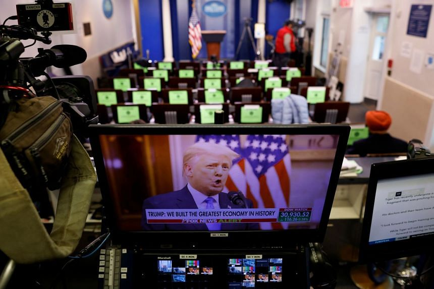 Mr Donald Trump, as seen on a TV monitor, making remarks during his last day in office from the White House Briefing Room.