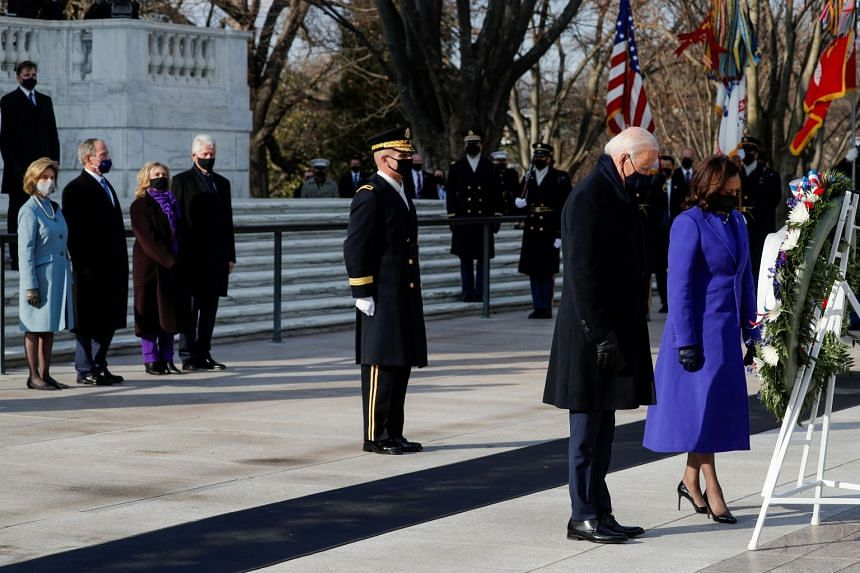 Joe Biden and Kamala Harris take part in a wreath-laying ceremony, with Bill Clinton, Hillary Clinton, George W. Bush and Laura Bush looking on.