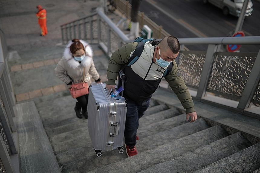 Travellers at a Beijing railway station on Tuesday. Those heading to rural villages will have to go through a 14-day isolation period as new cases of Covid-19 keep China on edge ahead of Chinese New Year. PHOTO: EPA-EFE