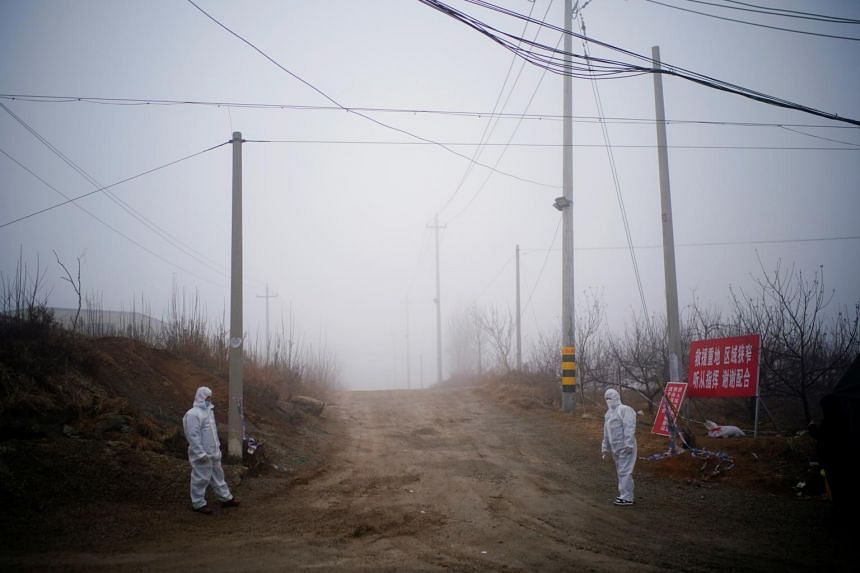Security members stand guard at an entrance to the Hushan gold mine in Shandong province, on Jan 21, 2021.