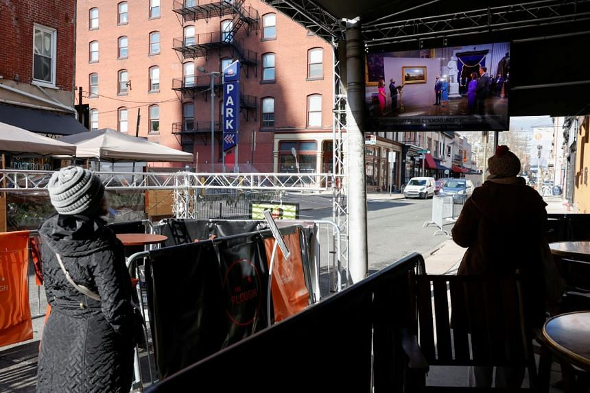 People watch the televised inauguration of US President Joe Biden in Philadelphia on Jan 20, 2021.