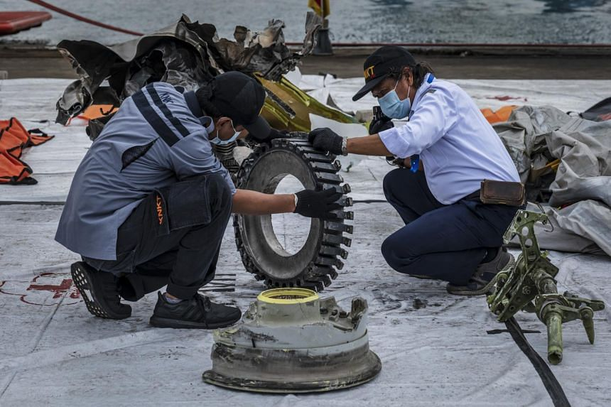 Safety officials examine wreckage from Sriwijaya Air Flight 182 at Tanjung Priok Port in Jakarta, on Jan 12, 2021.