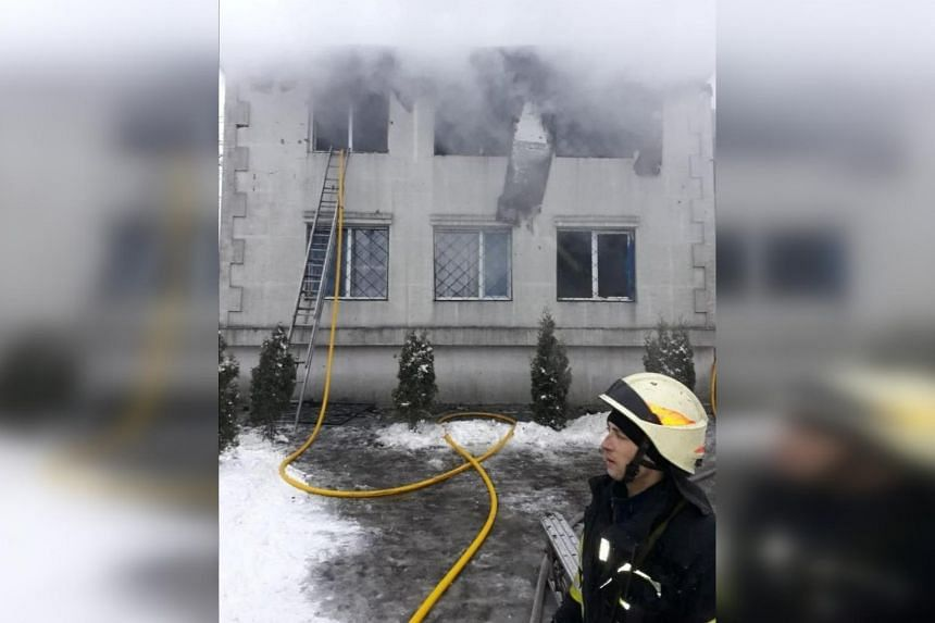 A rescuer works at the scene of the accident following a fire in nursing home in Kharkiv, Ukraine on Jan 21, 2021.