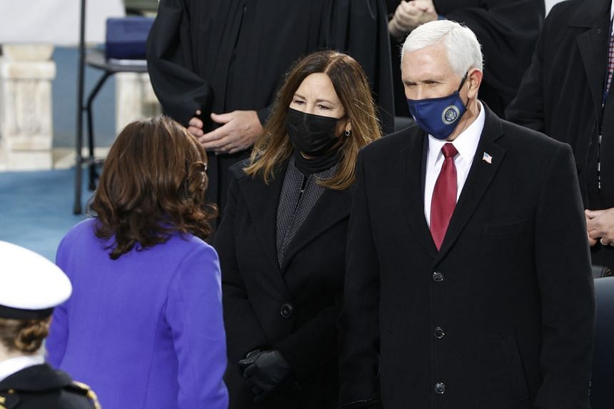 Outgoing US Vice-President Mike Pence and his wife Karen speak to vice-president-elect Kamala Harris at the inauguration of new President Joe Biden.