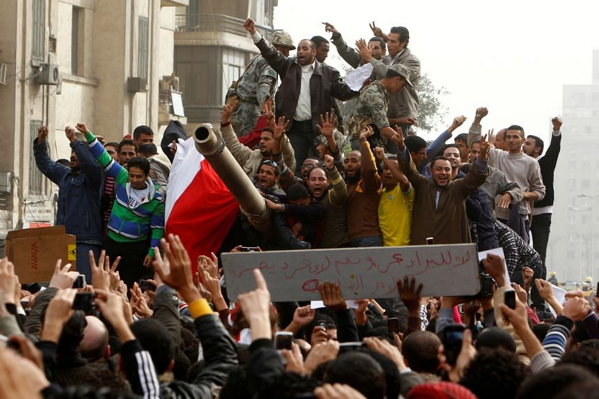 Demonstrators celebrate atop an army tank in Tahrir Square during protests in Cairo, on Jan 29, 2011.