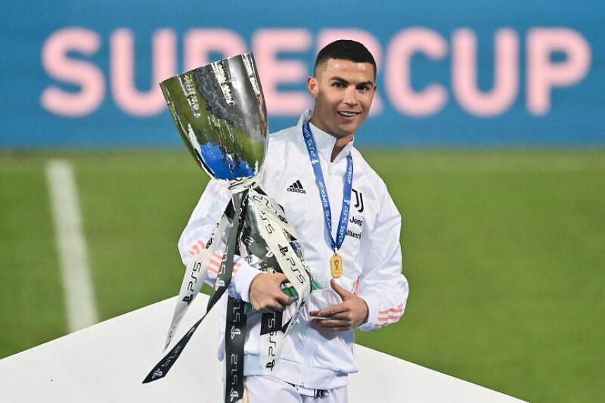 Juventus' Portuguese forward Cristiano Ronaldo poses with the winners' trophy after the Italian Super Cup football match, on Jan 20, 2021.