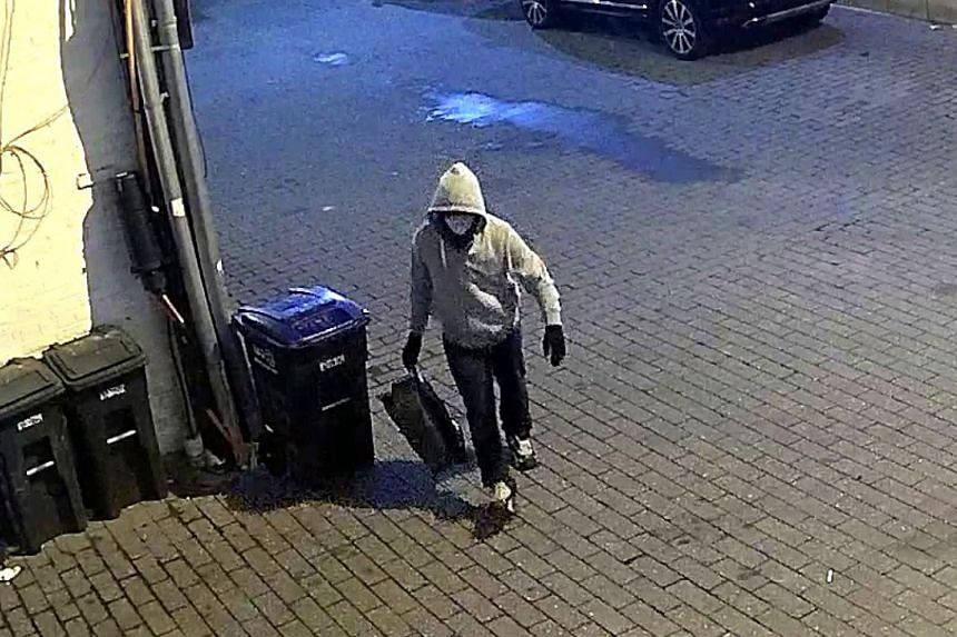 The suspect is seen in a security video wearing a loose grey hoodie, black gloves and a coronavirus mask.