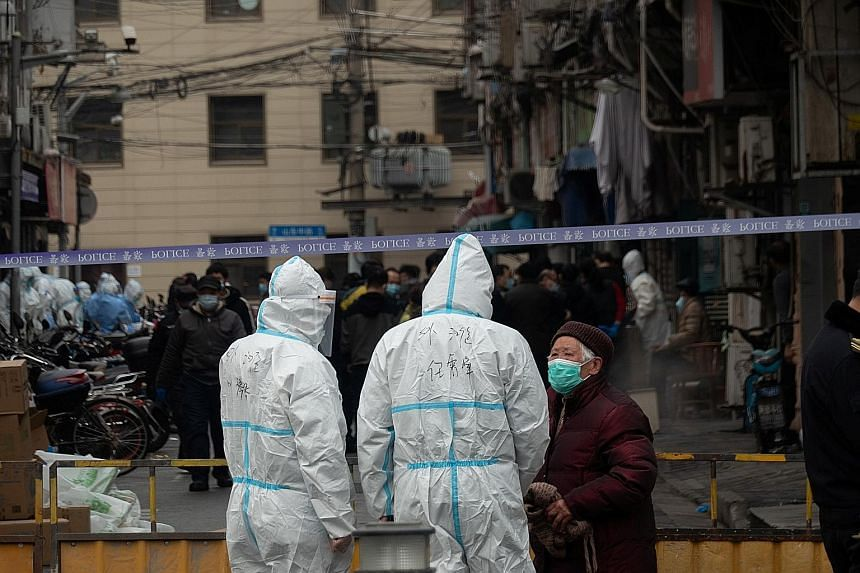 Workers clad in protective suits at an area that had been cordoned off near Renji Hospital in Shanghai yesterday, following a suspected case of coronavirus infection at the hospital. A total of 144 new Covid-19 cases were reported in China on Wednesd