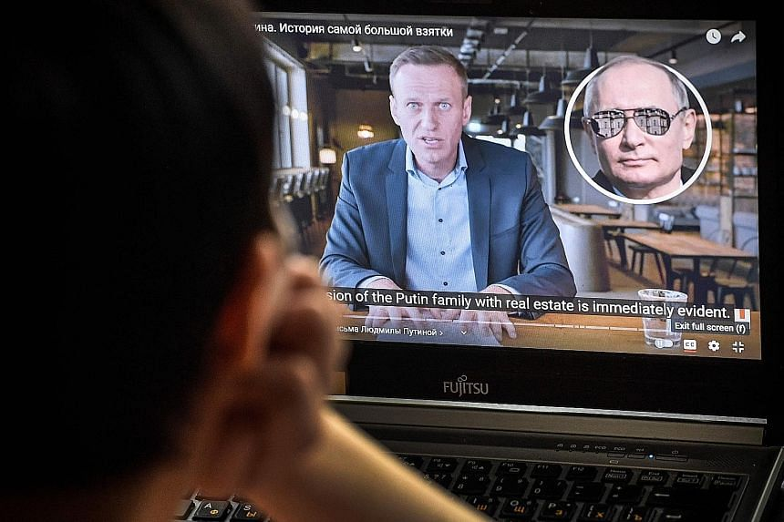 A woman in Moscow watching yesterday a video released online this week by Russian political activist Alexei Navalny's anti-corruption foundation. It reveals details of a lavish palace allegedly built for President Vladimir Putin (above) that overlook