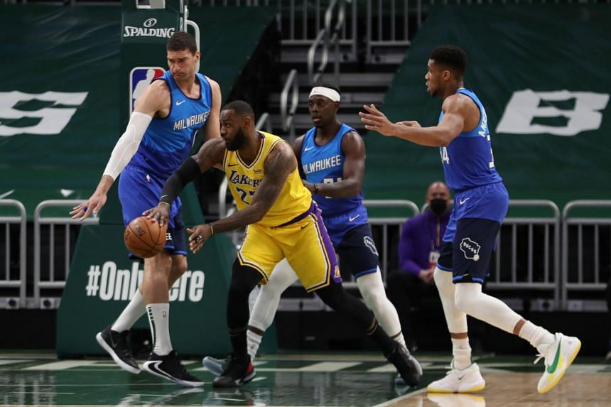 Los Angeles Lakers forward LeBron James (23) passes the ball away from Milwaukee Bucks players at the Bradley Center, on Jan 21, 2021.