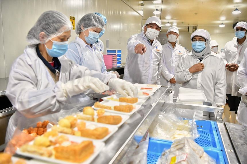 President Halimah Yacob (second from right) with Neo Group CEO Neo Kah Kiat during a visit to Thong Siek Food Industry, on Jan 22, 2021.