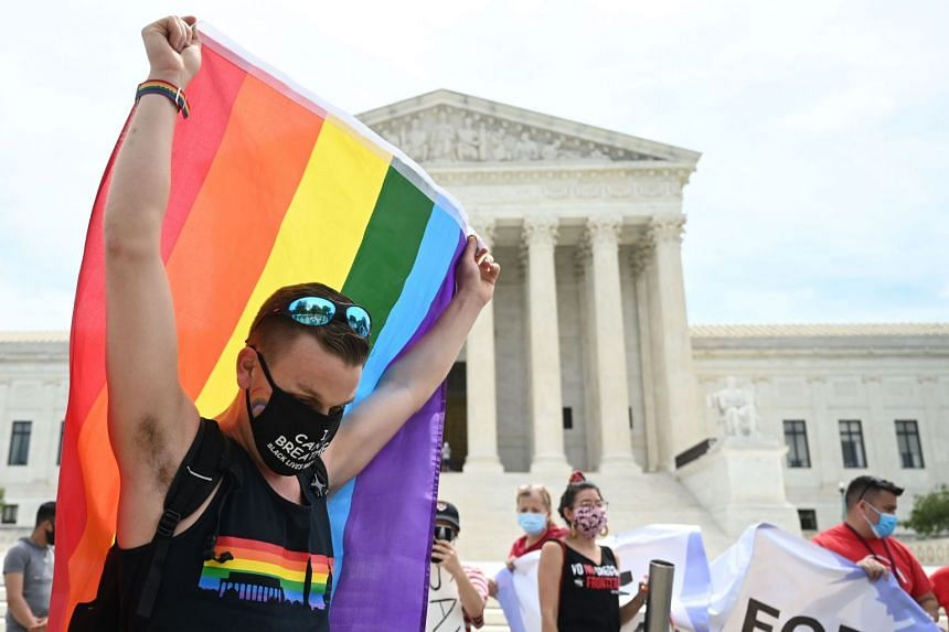 A 2020 photo shows a man waving a rainbow flag in front of the US Supreme Court after it decided that federal law protects LGBTQ workers from discrimination.