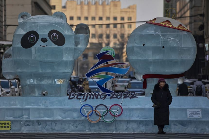 A woman stands next to an ice advertisement for the Beijing 2022 Olympics in Harbin, China, on Jan 11, 2021.