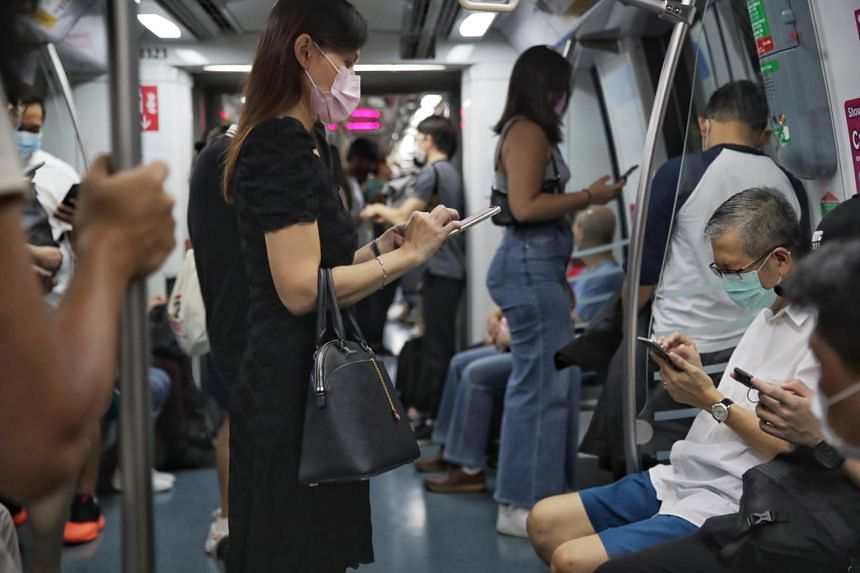 Commuters using their mobile phones while travelling on the MRT on Oct 7, 2020.