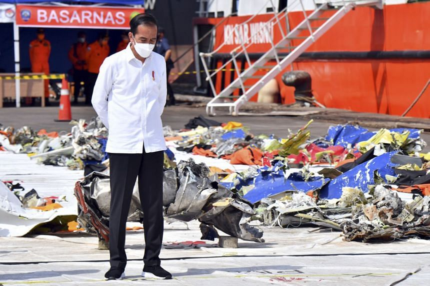 Indonesian President Joko Widodo beside the debris of Sriwijaya Air Flight SJ182 recovered from waters off Jakarta, during a visit to Tanjung Priok port in the country's capital on Wednesday.