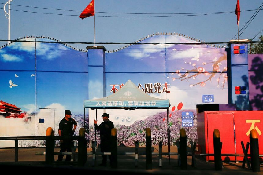 Security guards at the gates of what is officially known as a vocational skills education centre in Xinjiang Uighur Autonomous Region, in a file photo taken in September 2018. The entrance is adorned with Chinese flags and features giant prints of Ch