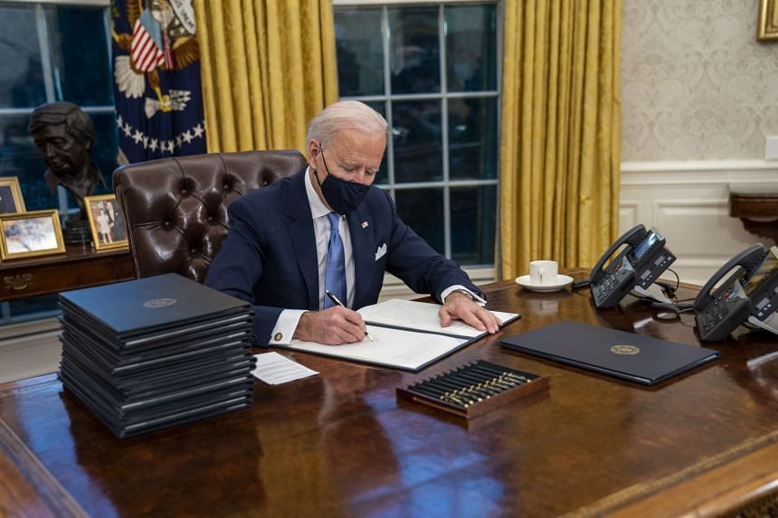 United States President Joe Biden signing the executive orders during his first minutes in the Oval Office at the White House on Wednesday, following his inauguration ceremony. He said the orders were just starting points, and that legislation would