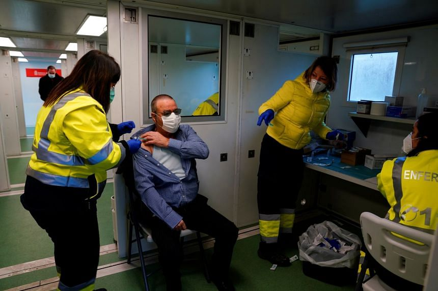 A man receives a coronavirus vaccine at a mobile medical station in Spain.