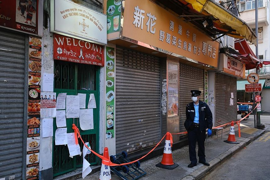 Left: Health workers assisting residents at mobile testing centres for Covid-19 in the Yau Ma Tei area of Yau Tsim Mong in Hong Kong yesterday. The lockdown is expected to begin this weekend, and involve 150 residential buildings in Yau Tsim Mong, ac