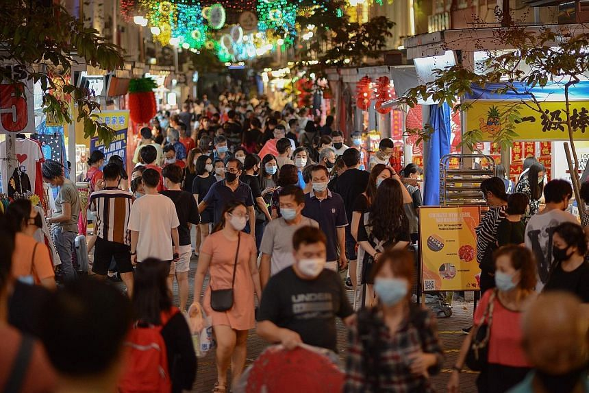 A bustling crowd of shoppers in Pagoda Street, in Chinatown, last Saturday. Education Minister Lawrence Wong urged the public to comply with the new measures.