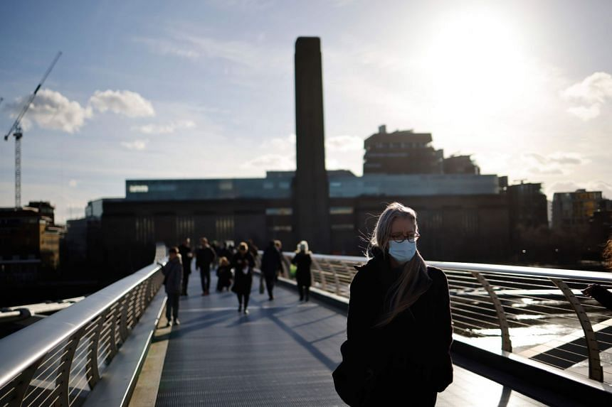 People walk across Millennium bridge in central London on Jan 22, 2021.