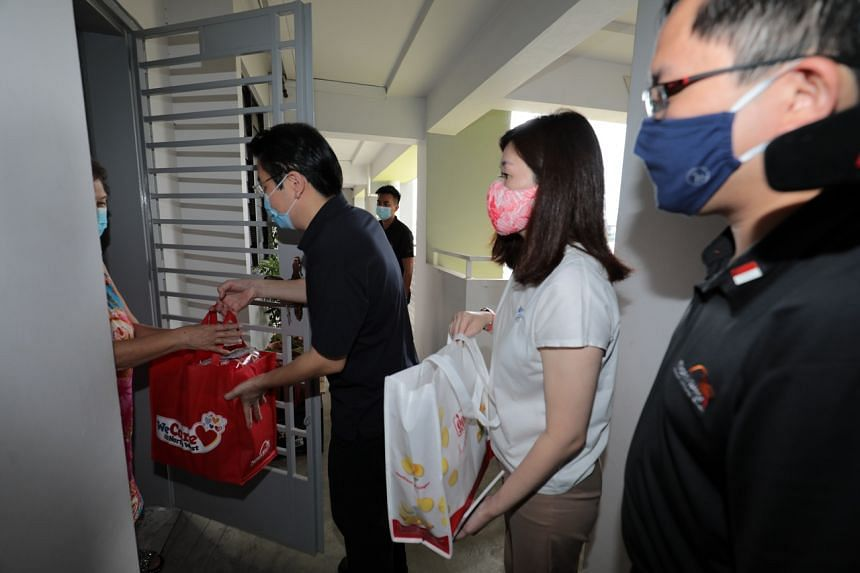 (Fom left) Education Minister Mr Lawrence Wong, together with Ms Hany Soh and Mr Alex Yam distributing festive packs to the residents on 23 Jan, 2021.