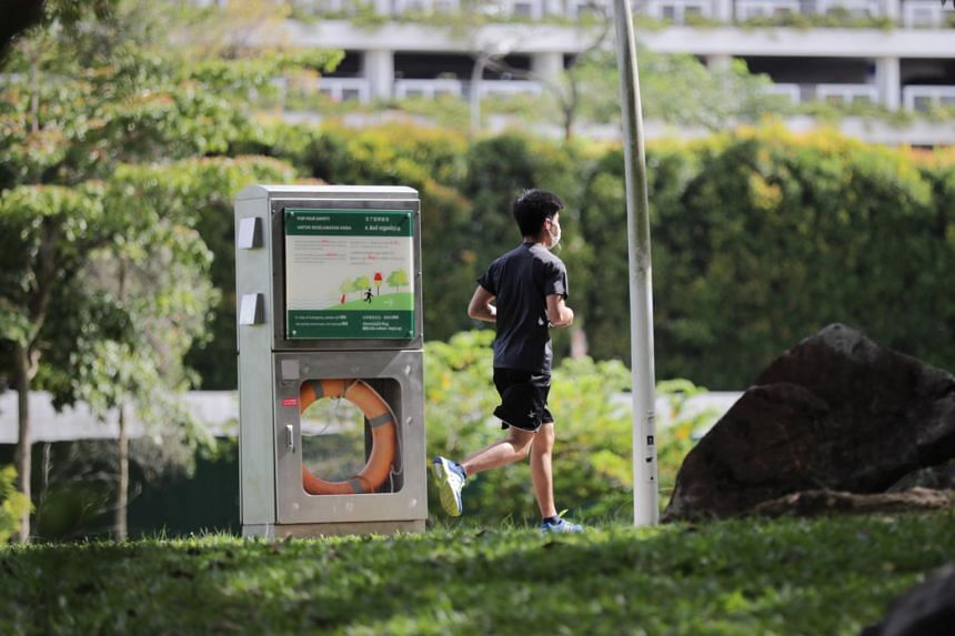 A man is seen wearing a mask while jogging in Bishan-Ang Mo Kio Park on April 22, 2020.