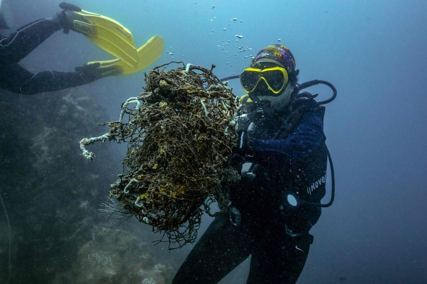Divers collecting discarded fishing nets in the waters off the coast of Chonburi province last month. The initiative aims to protect marine life and turn the nets into new plastic products such as face shields.